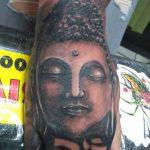 Buddha face tattoo on woman hand