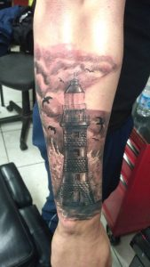 realistic lighthouse tattoo on arm
