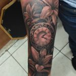 vintage clock with lily tattoo on arm